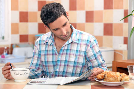 Man reading his newspaper at the breakfast table photo