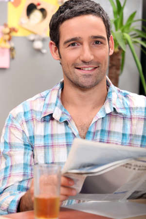 40 45: Man drinking a glass of apple juice while reading the newspaper Stock Photo