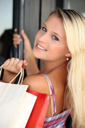 abriendo puerta: Adolescente rubia con bolsas de la compra Foto de archivo