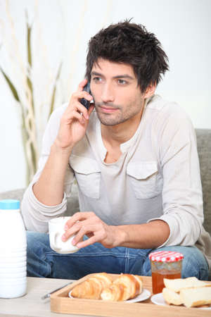 Man making a phone call over breakfast Stock Photo - 12251789