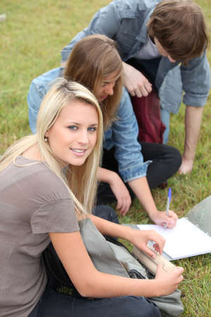 Three students studying in the park Stock Photo - 12251916