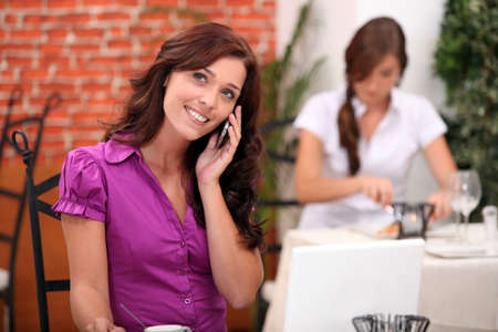 stood up: Young woman on cellphone in a restaurant Stock Photo