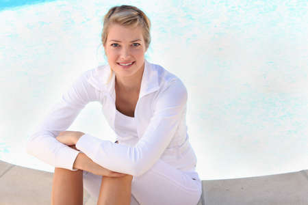 Young woman sitting next to a swimming pool Stock Photo - 12251215