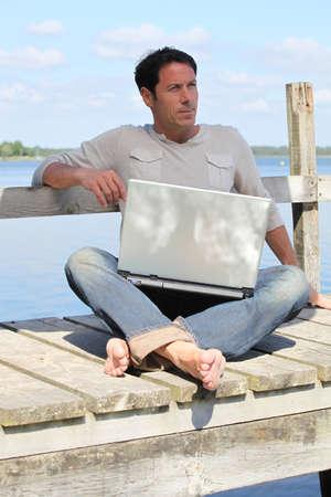 pies masculinos: El hombre en la computadora portátil junto a un lago Foto de archivo