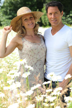 40 50: Couple in field of flowers. Stock Photo