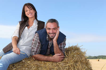 Farming couple sitting on a haystack photo