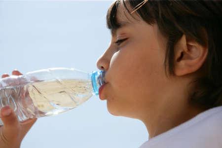 Boy drinking water in a bottle photo