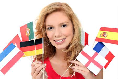 idiomas: muchacha que sostiene un manojo de banderas nacionales