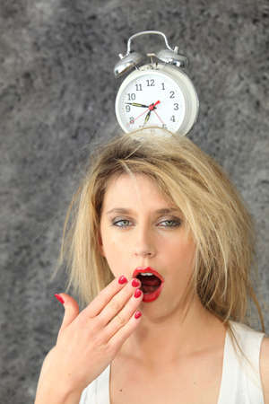 Blond woman with alarm clock on head photo