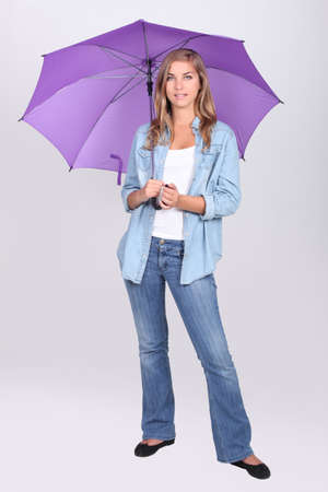 Young woman standing under a bright purple umbrella photo