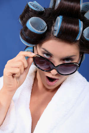 hot rollers: woman with curler wearing bath robe and sunglasses