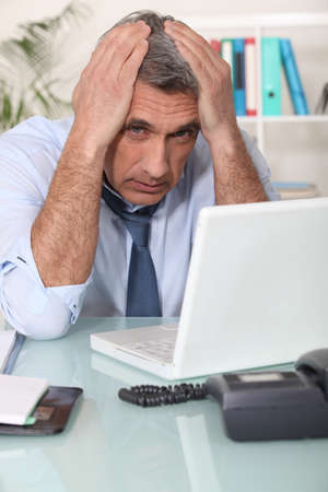 Stressed man using laptop photo
