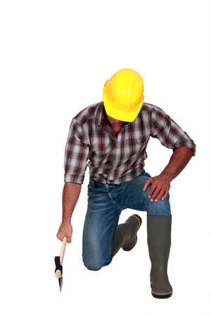 kneeling man: Tradesman using an axe