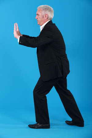 sideway: A mature businessman miming. Stock Photo