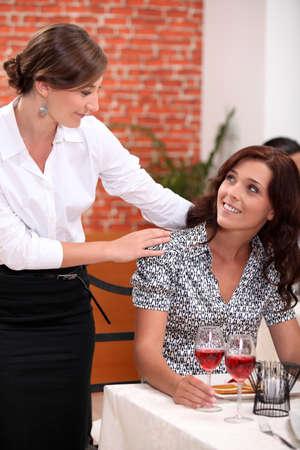 reassure: Waitress serving female customer