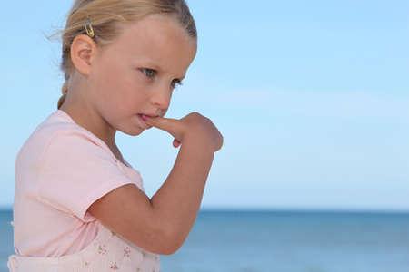 suck: Young girl biting her thumbnail Stock Photo