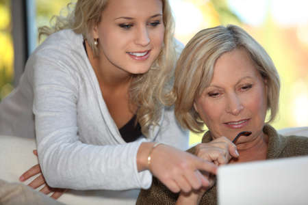Daughter showing mother how to use  the Internet photo