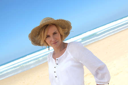 Angled shot of woman in a straw hat on a beautiful sandy beach photo