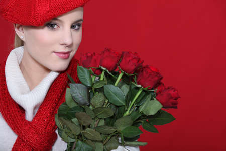 A cute blond holding a bunch of roses. photo