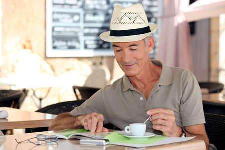 senior gentleman enjoying free time in cafe photo