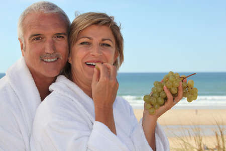toweling: Couple eating grapes for breakfast on the  beach