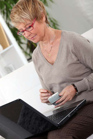 Senior woman in front of a laptop at home photo