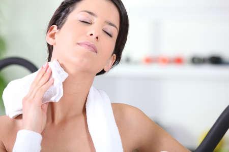 sudoracion: La mujer se limpia con una toalla en el gimnasio Foto de archivo