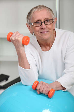 reestablishment: Elderly woman lifting weights in gym Stock Photo