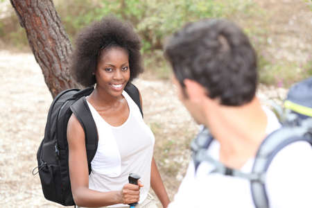 looking around: Interracial couple hiking in the forest