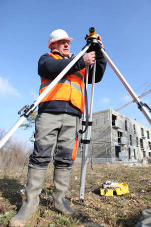 leveling: A land surveyor using an altometer