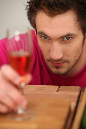 Determined man looking at a wine glass photo