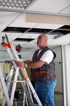 office ceiling: Electrician working on ceiling