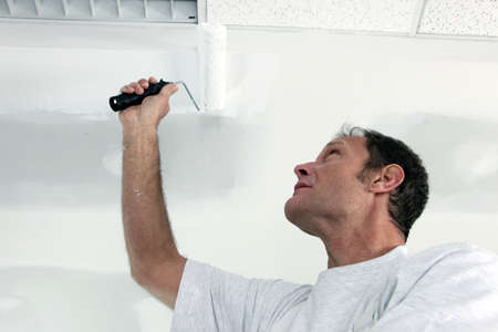 Painter using roller on ceiling photo