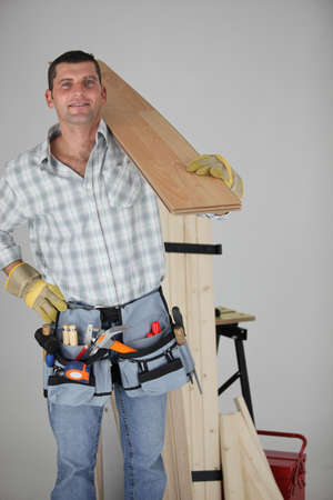 Carpenter carrying a wooden plank photo