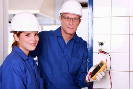 jumpsuite: an electrician and his female colleague checking an electrical outlet