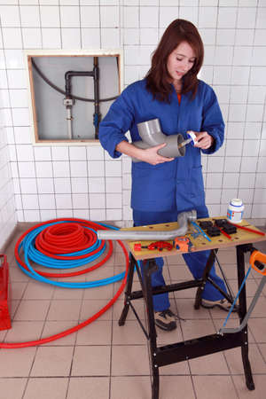 Female plumber glueing pipe together photo