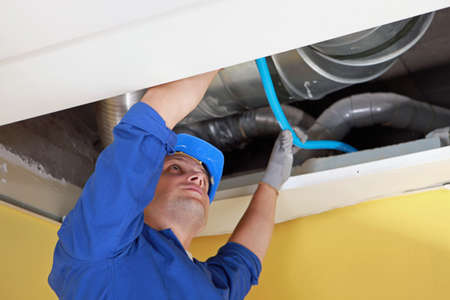 air duct: Worker holding blue pipe in place under air ducts