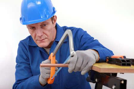 koperen leiding: Arbeider zagen koperen buis