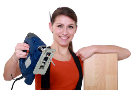 labourer: Female labourer holding band saw Stock Photo