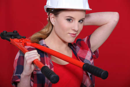Woman carrying bolt-cutters over shoulder Stock Photo - 12302476