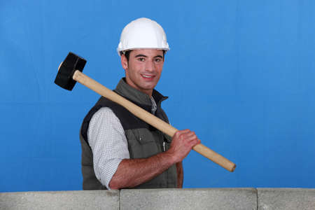 Tradesman holding a mallet and standing behind a low wall photo