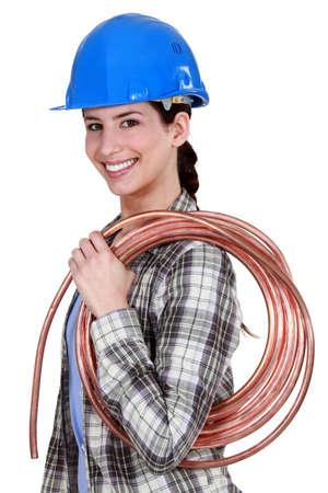 Female plumber holding pipe photo