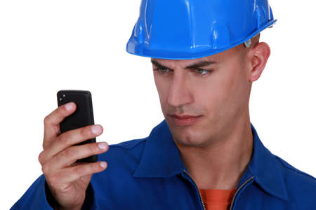 head collar: portrait of young blue collar reading sms against white background Stock Photo