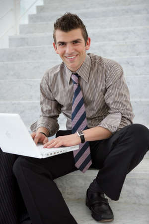stairwell: Young executive using a laptop computer on a stairwell Stock Photo