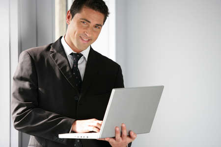 Man stood in office holding laptop Stock Photo - 12302833