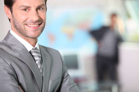 Businessman smiling with arms folded photo