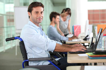 employee in wheelchair with laptop photo