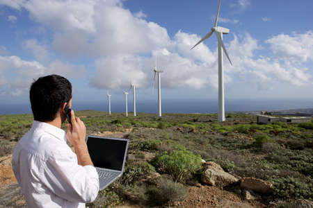 nonpolluting: Young businessman on phone next to wind turbines