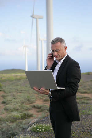 Businessman using his laptop and phone in the middle of nowhere photo