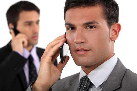 implacable: Les hommes d'affaires parlent sur leurs t�l�phones mobiles